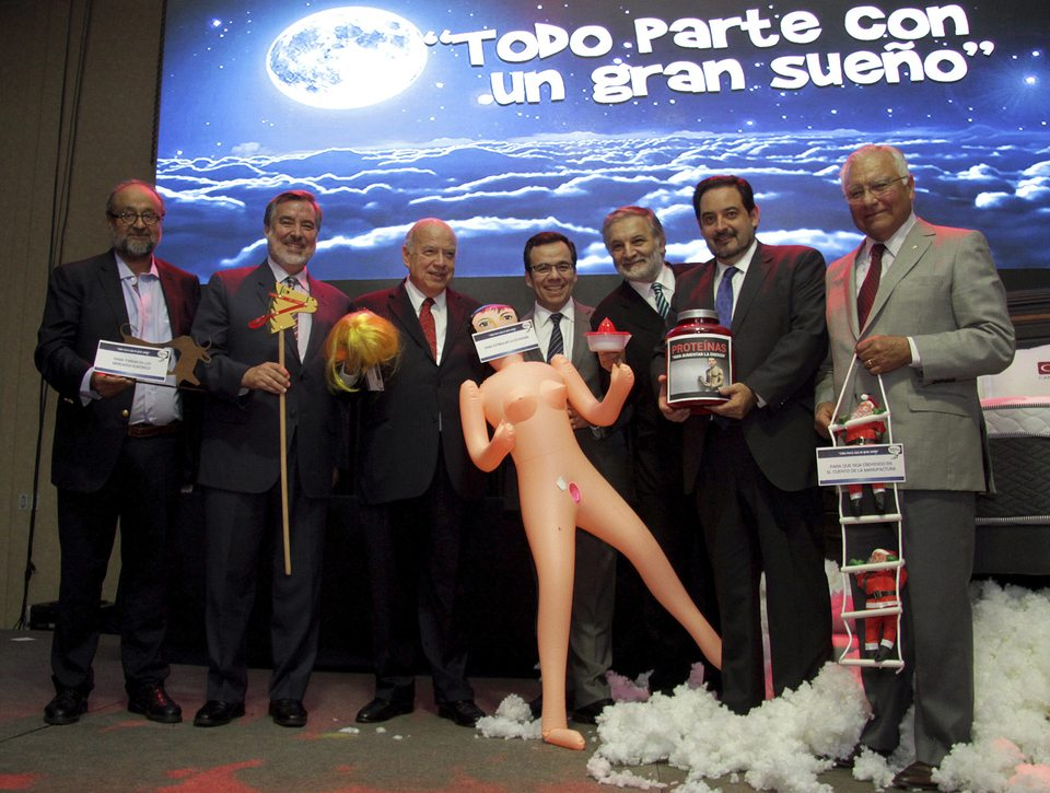"ProChile Director Roberto Paiva, from left to right, Chilean Sen. and ruling party presidential hopeful Alejandro Guillier, former OAS General Secretary Jose Miguel Insulza, Chile's Economy Minister Luis Cespedes, Ministry of Planning Executive Secretary Eduardo Britan, Energy Minister Andres Rebolledo and Asimet President Juan Carlos Martinez, pose for a photo with a gift of an inflated sex toy, a placard taped over its mouth that reads in Spanish: ""To stimulate the economy"",  during the Asexma exporters' association annual dinner, in Santiago, Chile,  in Santiago, Chile, Monday, Dec. 13, 2016. Politicians and businessmen laughed and posed for the cameras, but later social networks exploded in criticism that pointed to the sexist nature of the gift. (AP Photo/Jorge Cadenas)"
